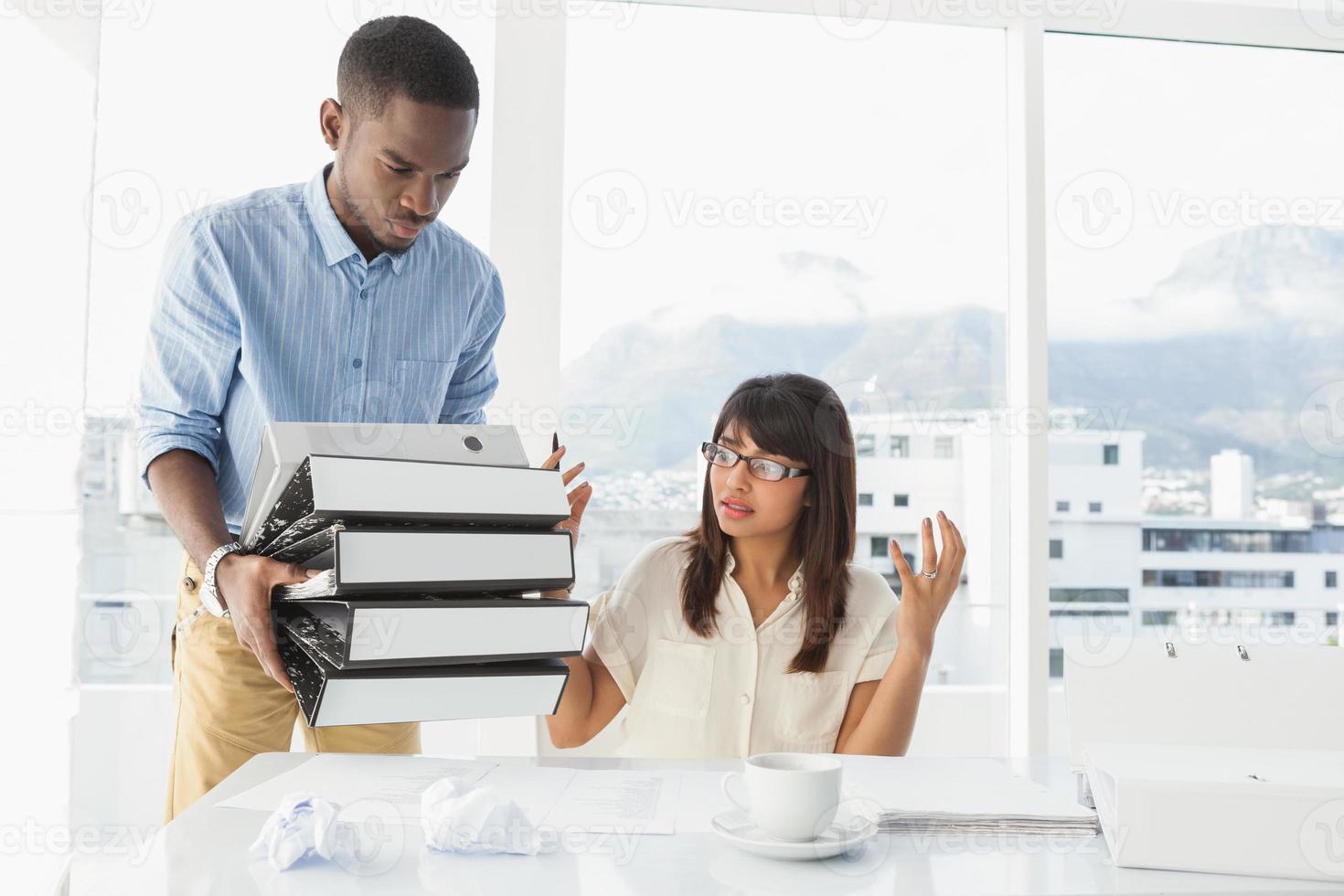 homem dando pilha de arquivos para seu colega exasperado foto