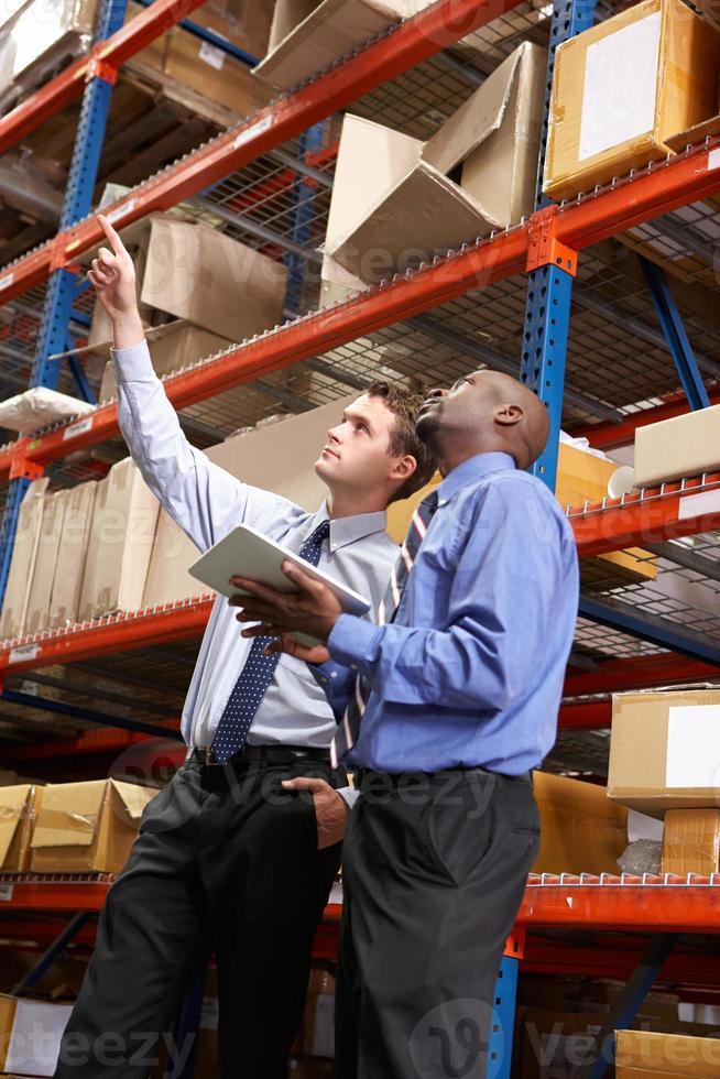 dois empresários com tablet digital em armazém foto