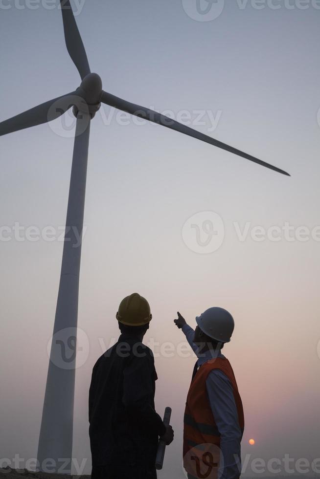 engenheiros ao lado de uma turbina eólica ao pôr do sol foto