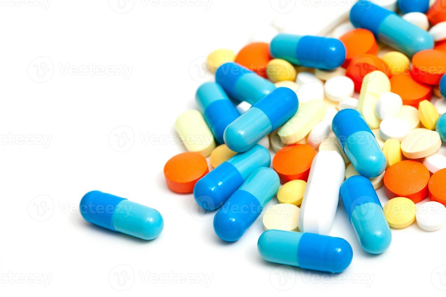 pílulas coloridas em fundo branco foto
