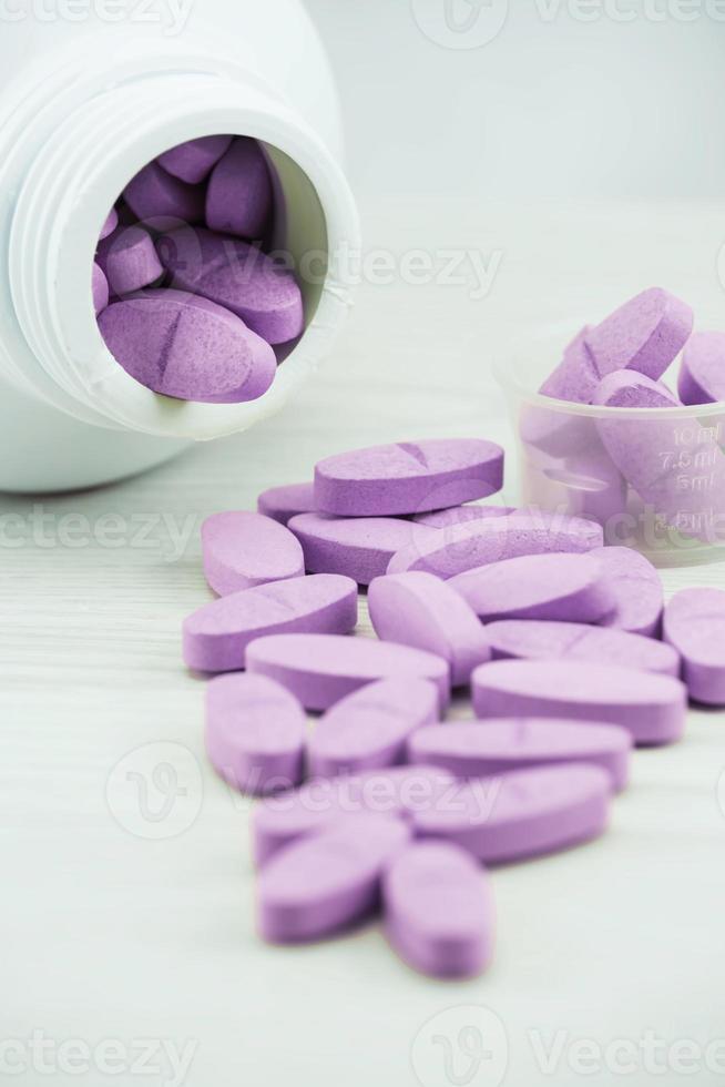 pílulas violetas um frasco de comprimidos em cima da mesa. foto