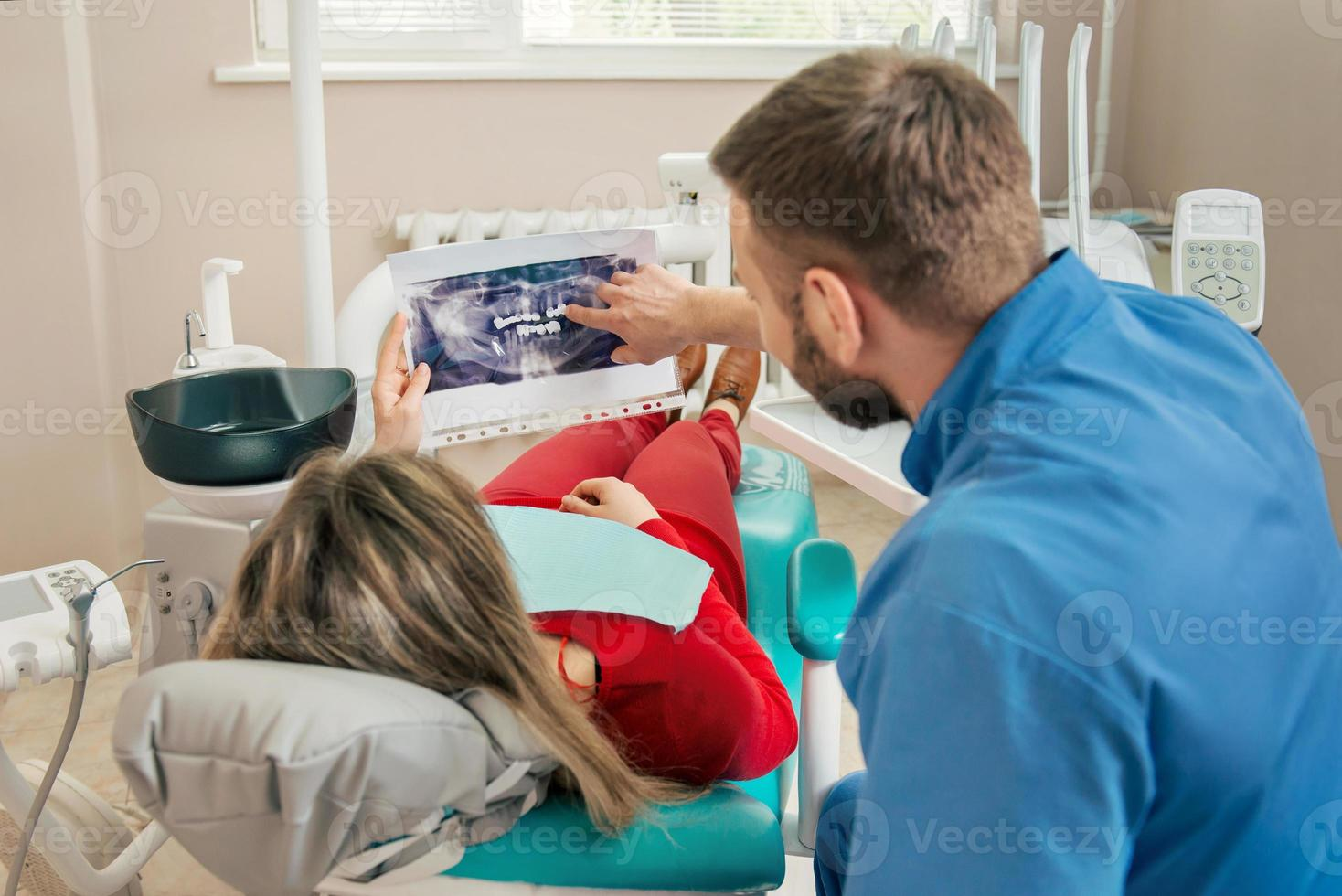 dentista mostrando paciente sua imagem de dentes de raio-x foto