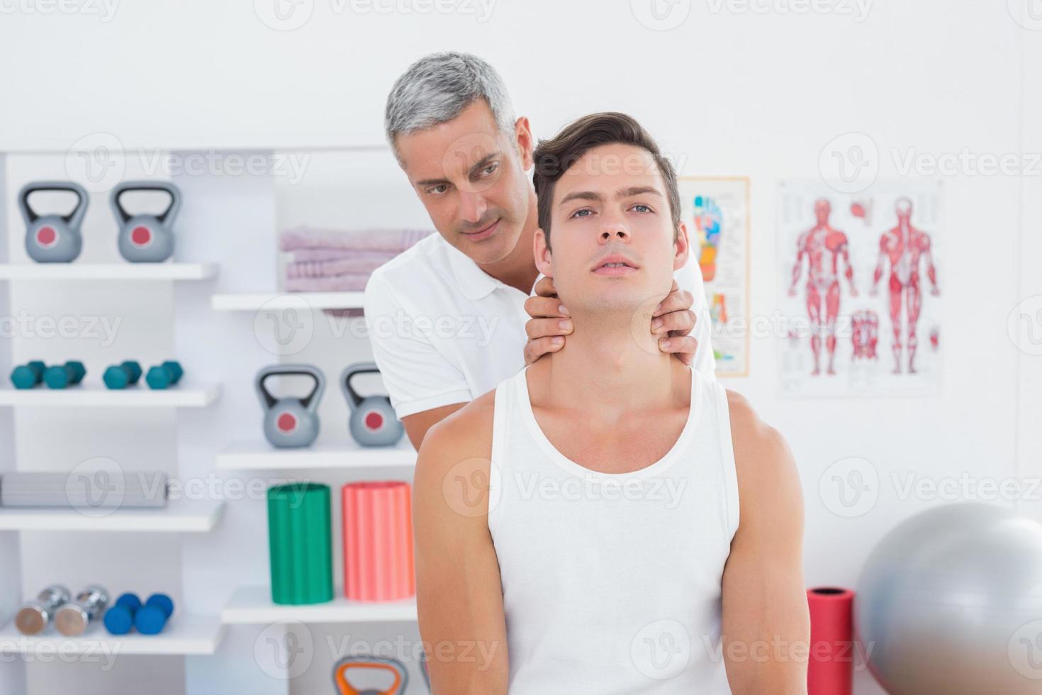 médico massageando um pescoço jovem foto