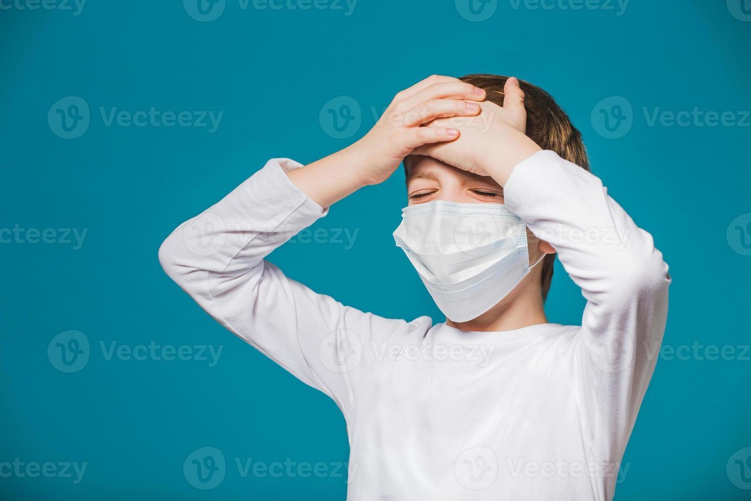 retrato de menino usando máscara de proteção com dor de cabeça foto