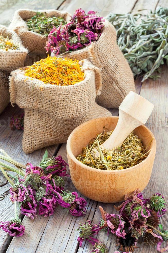 ervas medicinais em argamassa de madeira e em sacos de juta foto