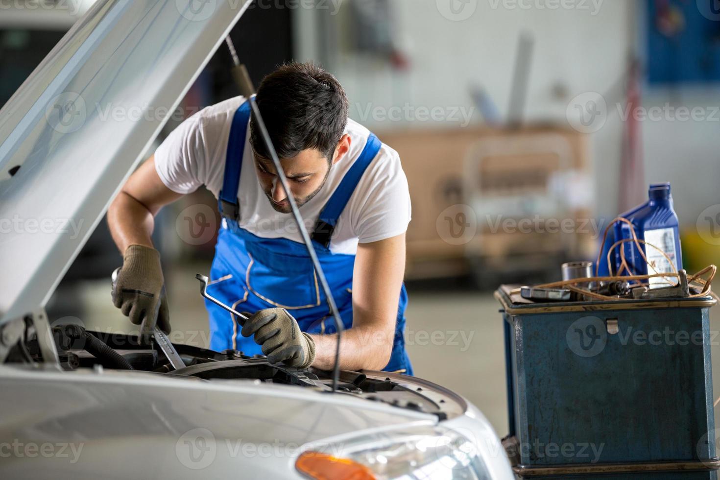 mecânico de automóveis trabalhando sob o capô foto