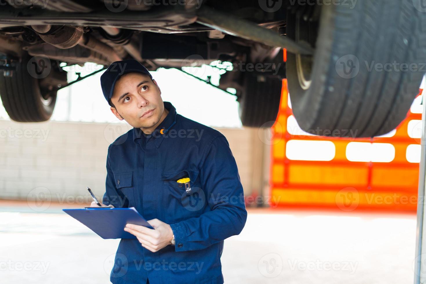 mecânico de automóveis, trabalhando em um carro em sua garagem foto