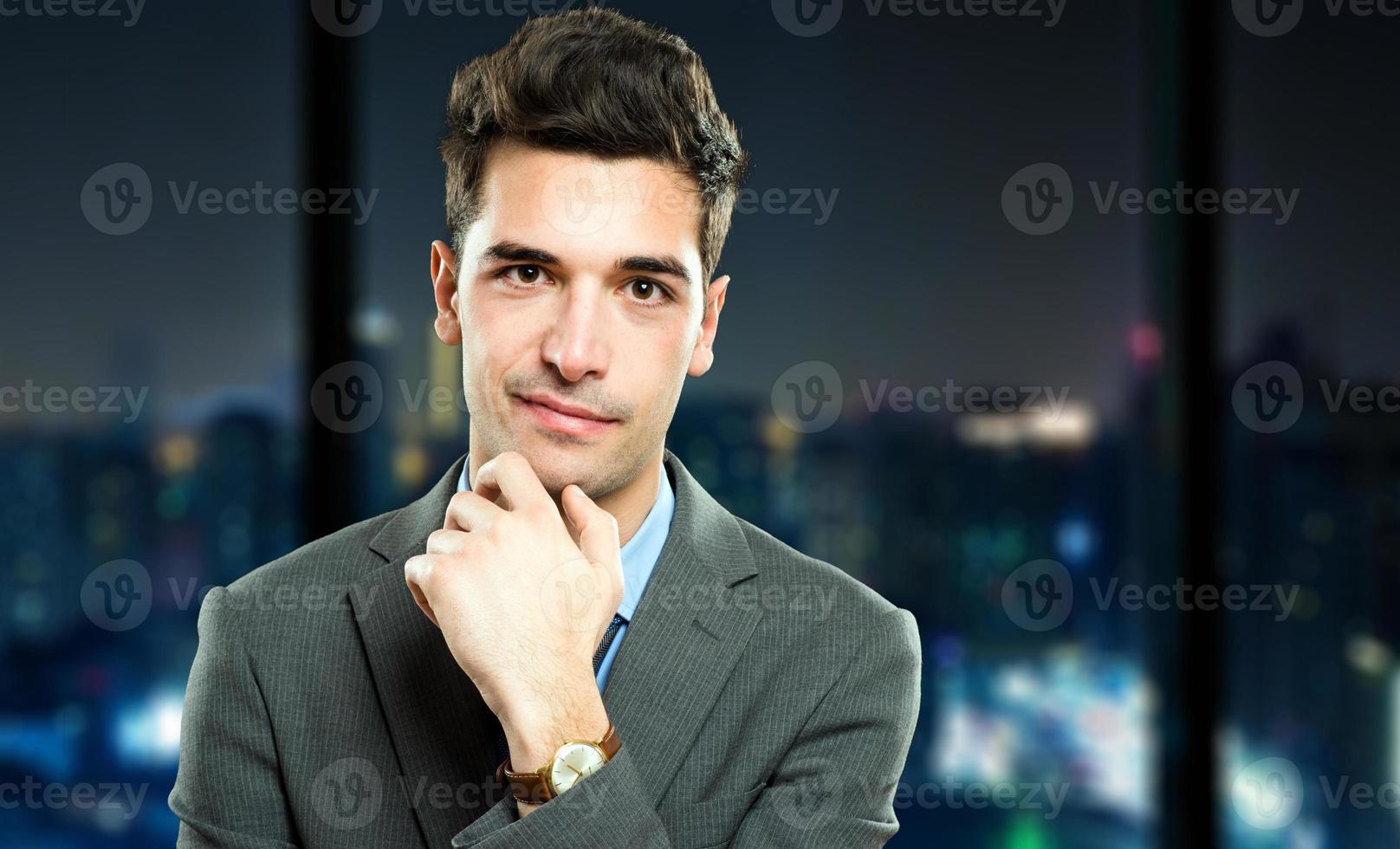 jovem gerente em seu escritório durante a noite foto