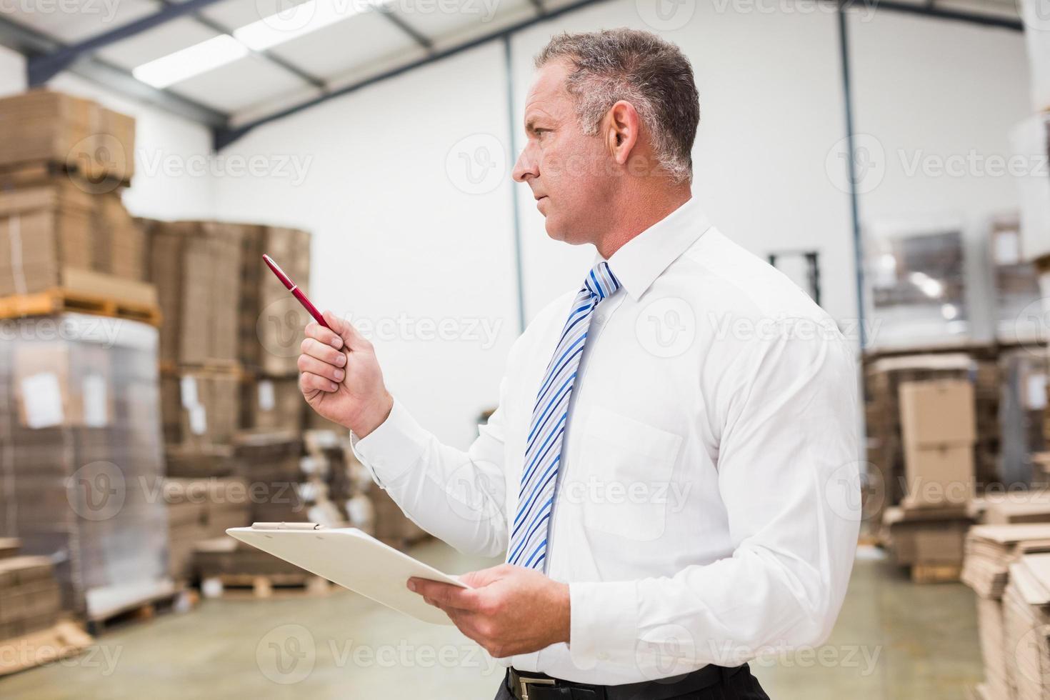 chefe de armazém, verificando seu inventor foto