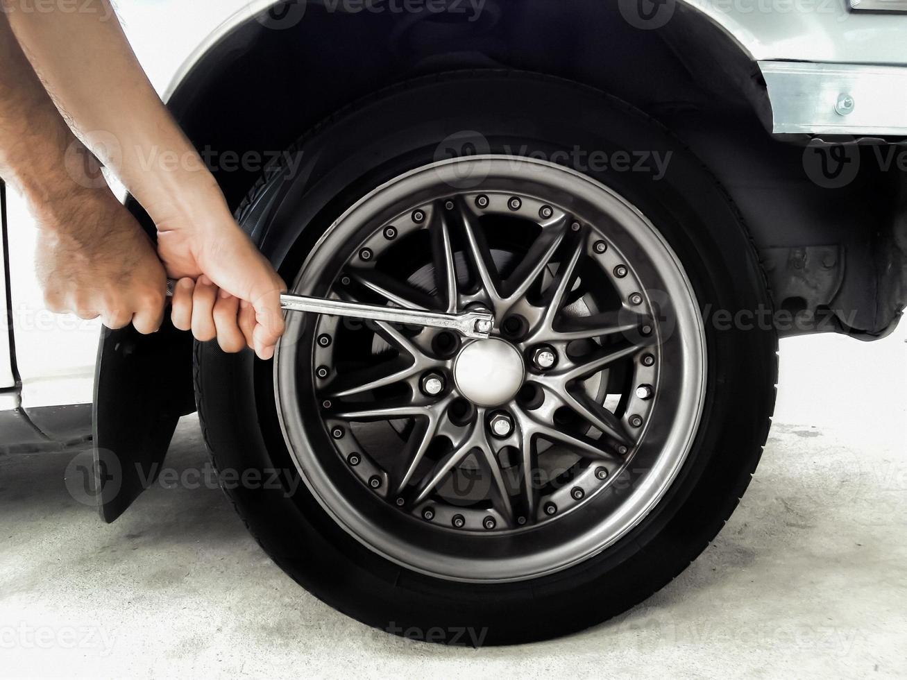 remover as porcas das rodas com uma chave de mão foto
