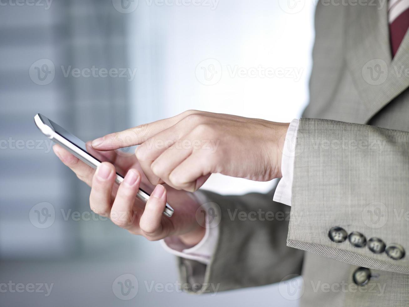 mãos do empresário usando um smartphone foto