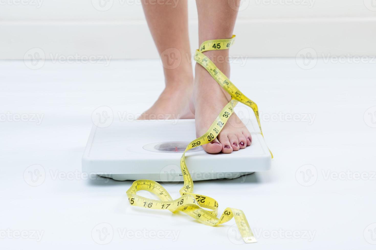 pés femininos em pé em uma balança de banheiro e fita métrica foto