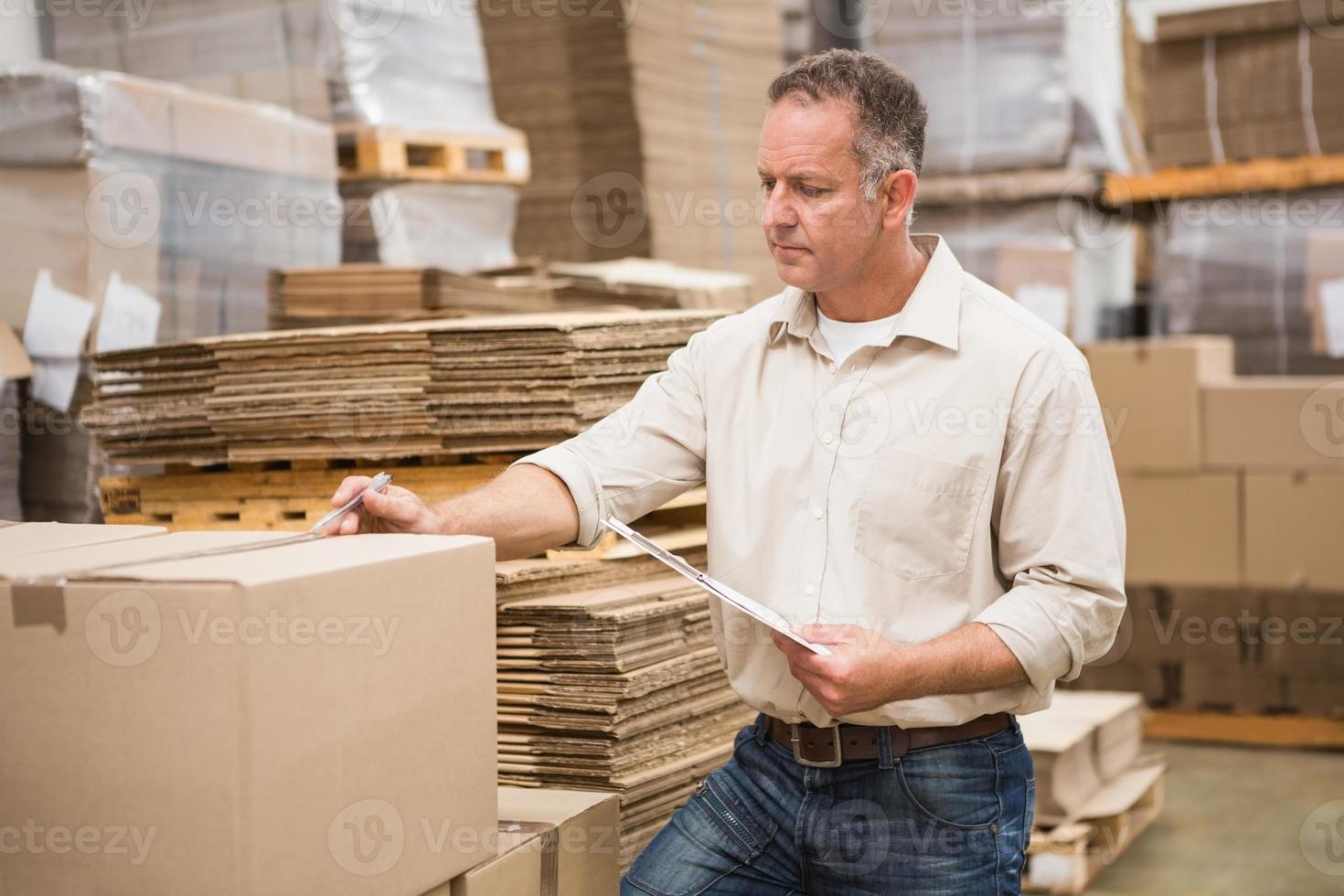 trabalhador de armazém, verificando sua lista na área de transferência foto