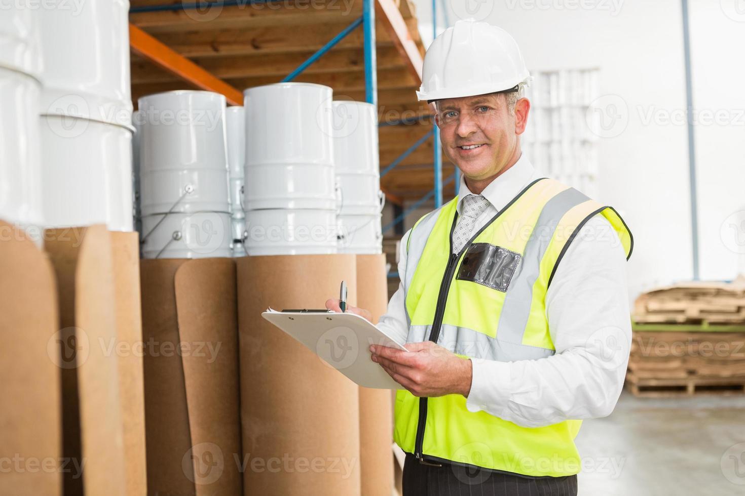 gerente de armazém, verificando sua lista na área de transferência foto