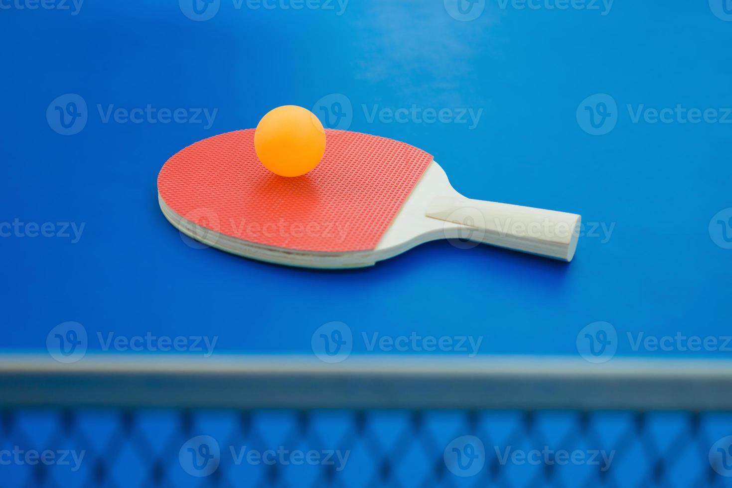 raquete de pingue-pongue e bola e rede na mesa de pingue-pongue foto