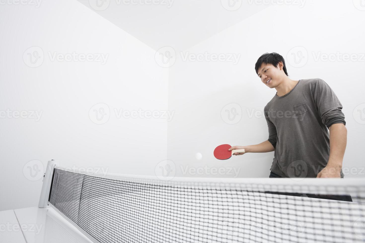 homem adulto médio asiático jogando ping-pong foto