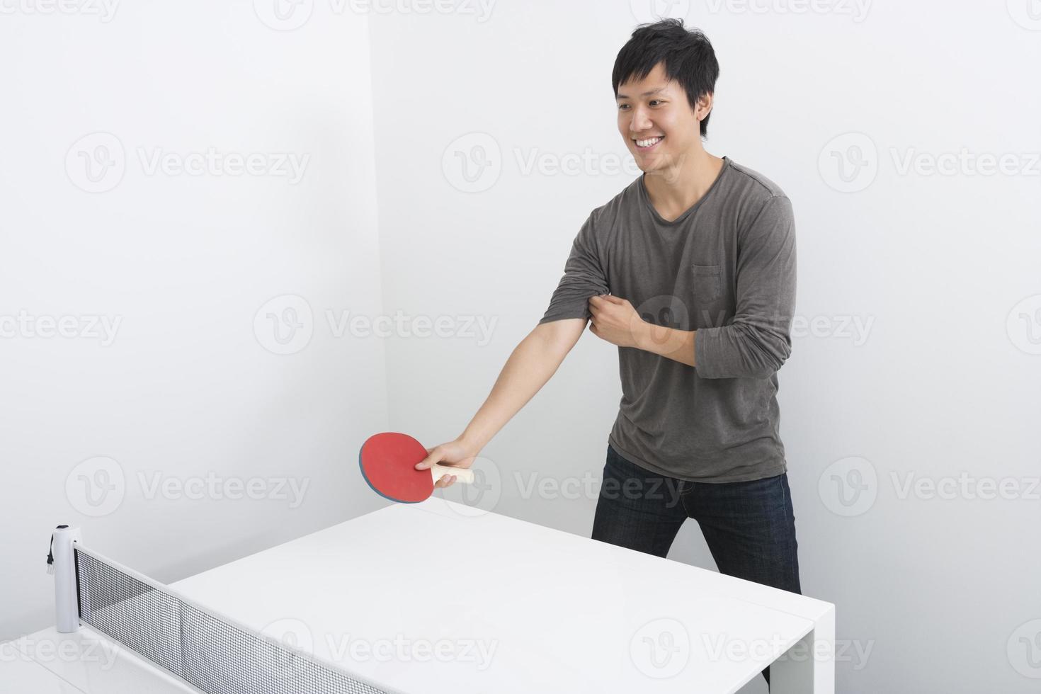 bonito homem adulto médio jogando tênis de mesa foto