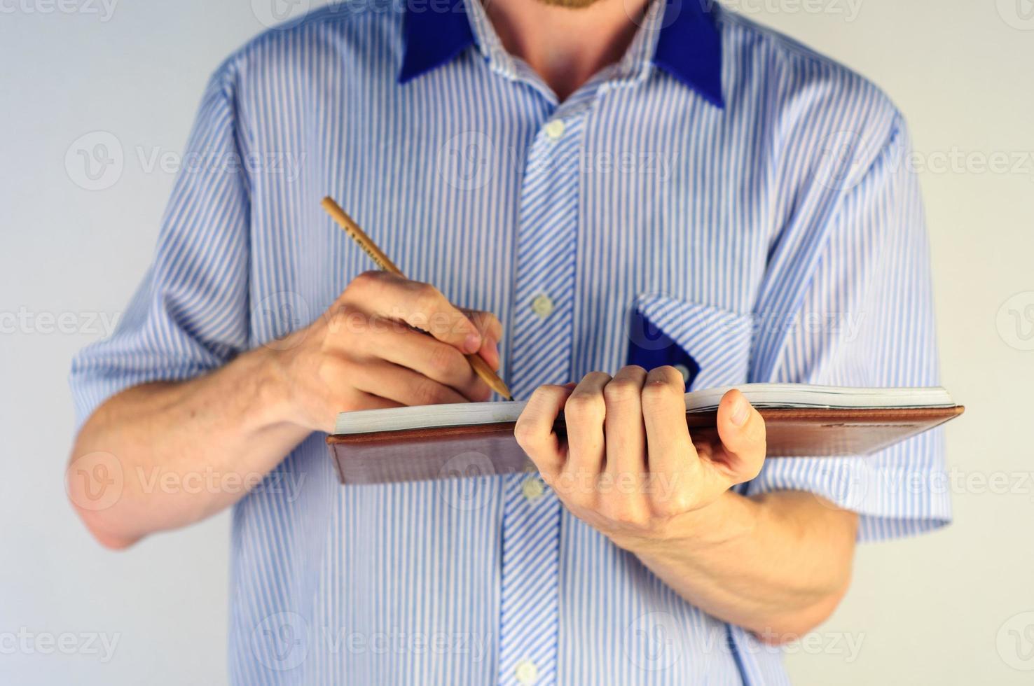 homem de camisa, escrevendo em seu caderno foto