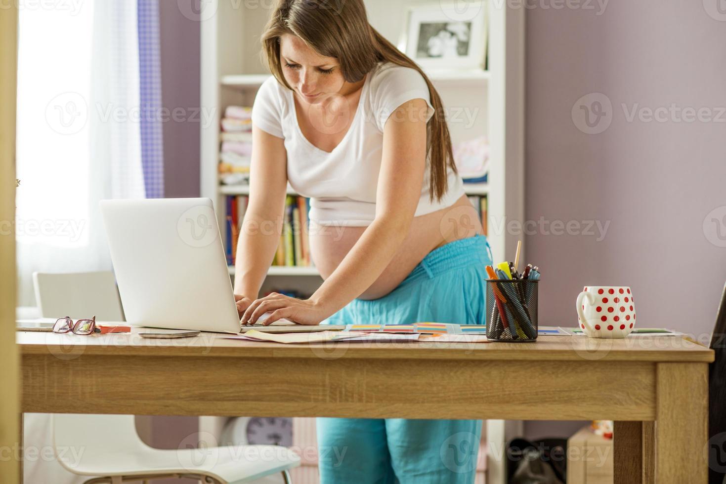 mulher grávida trabalhando em casa foto