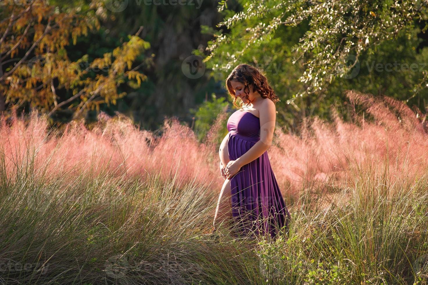 mulher grávida sorridente em pé na folhagem colorida foto