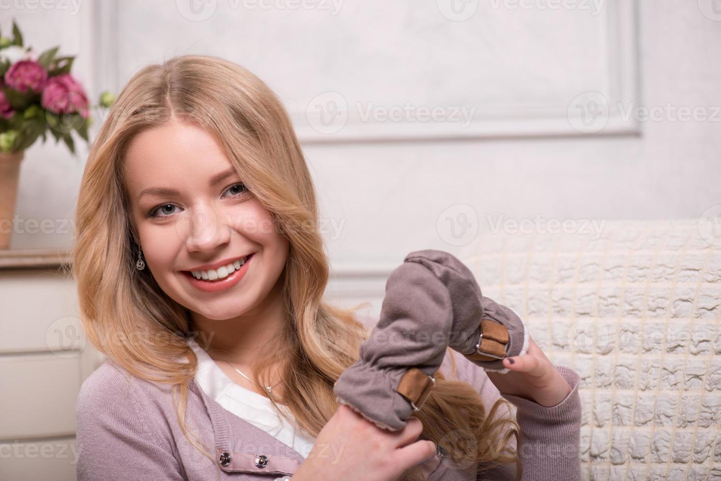 jovem mulher atraente segurando luvas de bebê, tiro interior foto