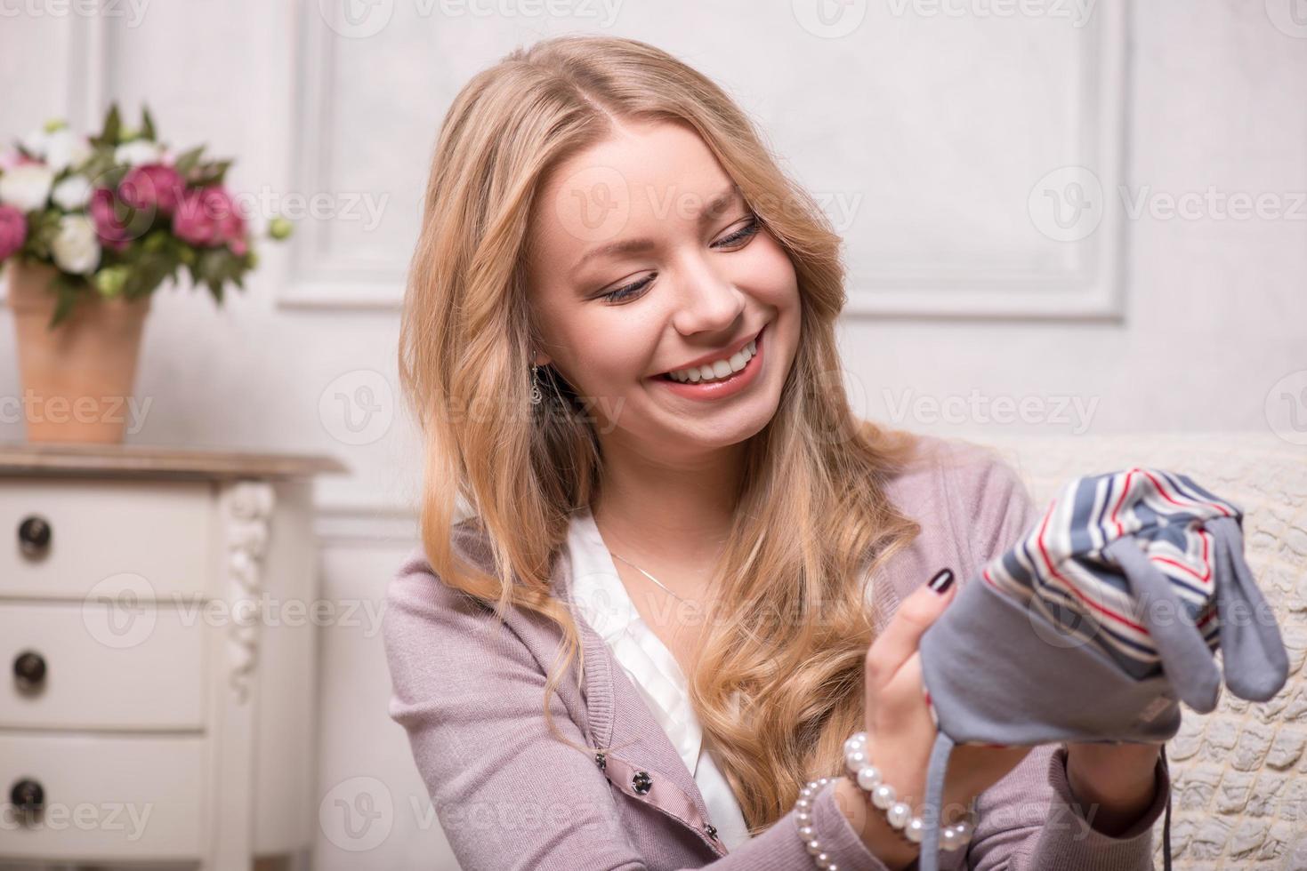 jovem mulher atraente, segurando o chapéu do bebê, tiro interior foto