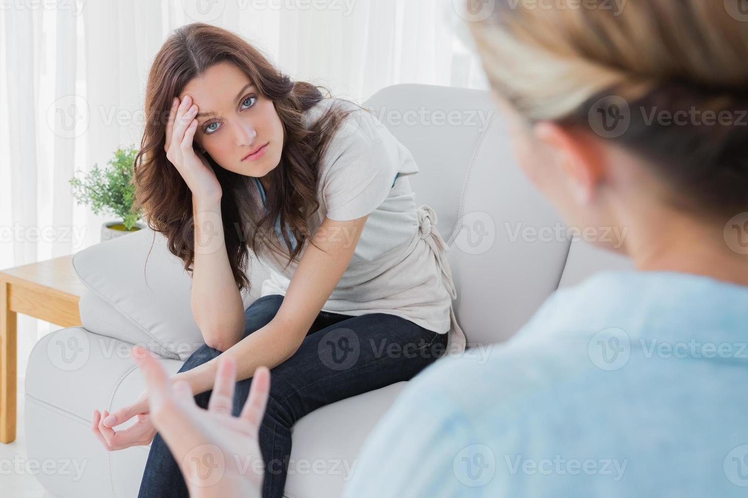 mulher preocupada, sentado e olhando para a câmera durante a terapia foto