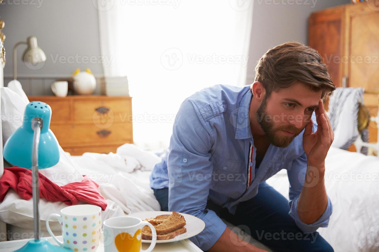 homem que sofre de depressão, sentado na beira da cama foto