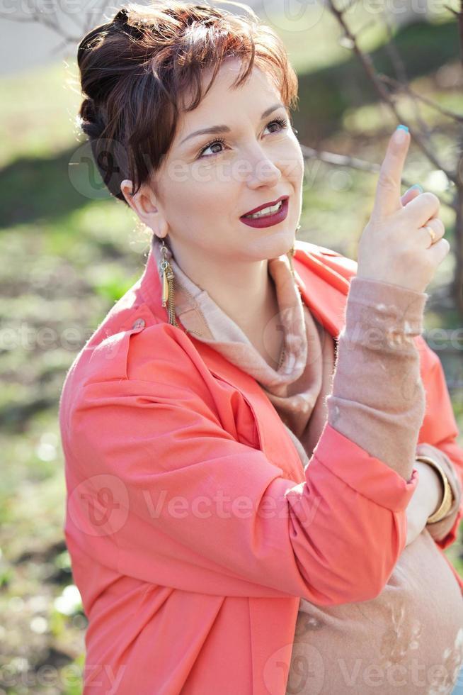 bela jovem mulher grávida na primavera ao ar livre foto