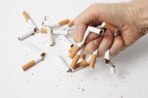 quebrando cigarros para parar de fumar no fundo branco foto