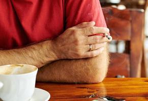 mão do homem com um cigarro foto