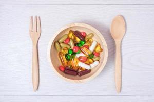 medicamento e vitamina na tigela de madeira foto
