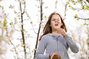 garota com alergia ao ar livre. a menina espirra foto