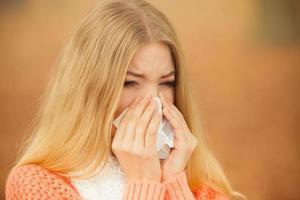 mulher doente doente no parque outono espirros em tecido. foto