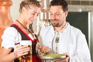 cervejeiro e mulher com copo de cerveja na cervejaria foto