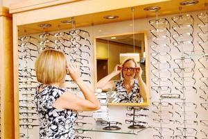 senhora experimentando óculos