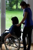 cuidador empurrando cadeira de rodas com mulher com deficiência foto