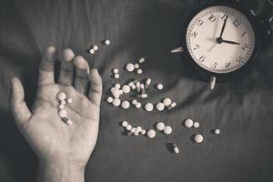 overdose mão de homem e drogas na cama à noite foto