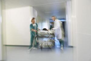 médicos que movem o paciente na maca através do corredor do hospital foto