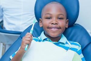 garoto segurando a escova de dentes na cadeira do dentista foto