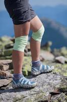 atleta de mulher está saltando sobre pedras nas montanhas foto