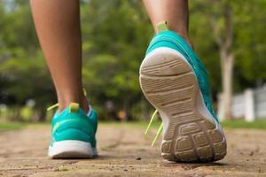 pés de corredor correndo na estrada closeup no sapato foto
