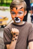menino com tigre de pintura de rosto foto
