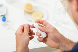 mãos segurando uma garrafa nasal foto