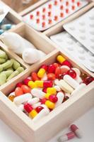 comprimidos médicos e ampolas em caixa de madeira foto