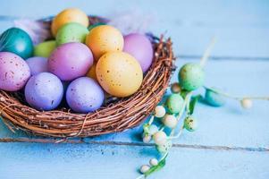 ovos de páscoa no ninho sobre fundo azul de madeira foto
