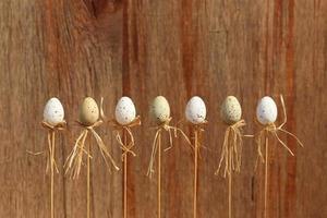 ovos de páscoa feliz em varas fundo marrom foto
