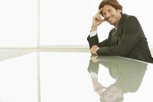 empresário sorridente, sentado na mesa de conferência foto