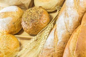 pão e trigo no fundo madeira, tonificação quente, seletiva foto