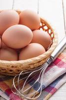 ovos de galinha em uma tigela sobre fundo de madeira foto